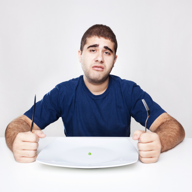 Junger Mann sitzt vor Teller mit einer Erbse