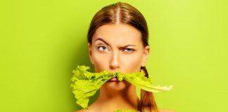 Frau mit einem Salatblatt im Mund