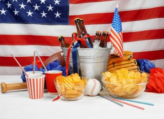 amerikanisches Flagge mit Chips, roten Getränkebechern und Bierflaschen