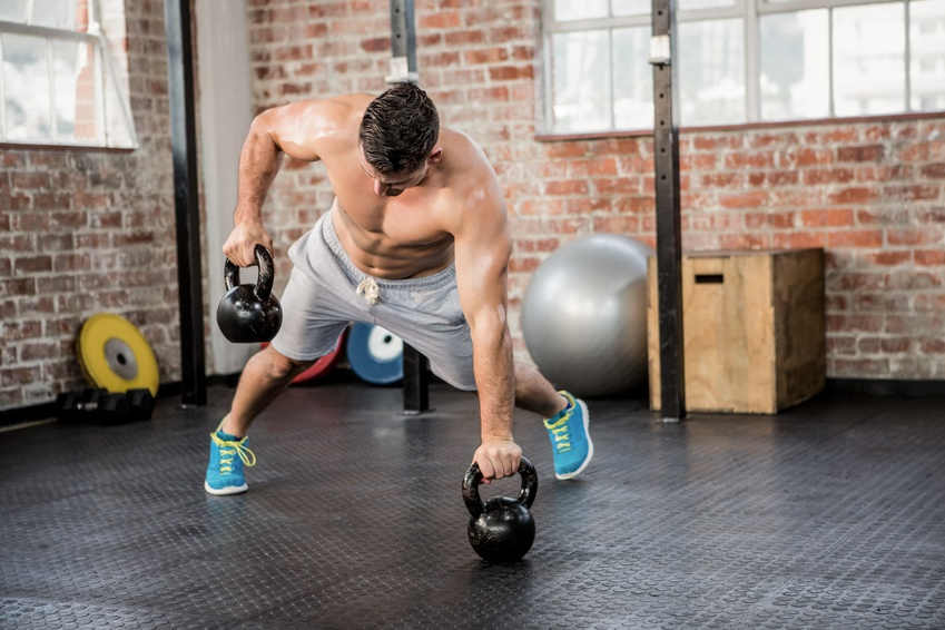 Shirtless man lifting kettlebell