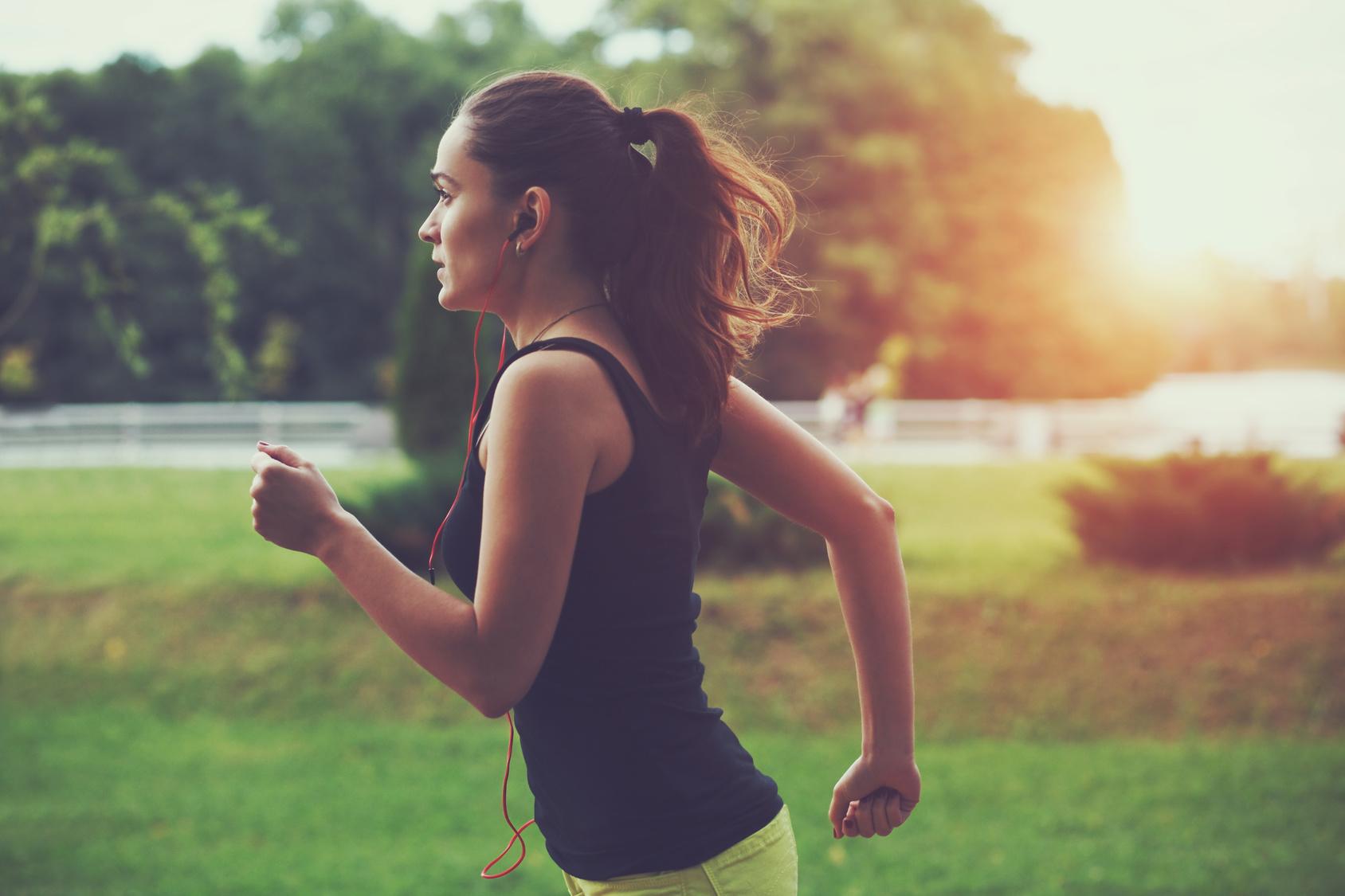 Frau joggt im Park bei Sonnenaufgang