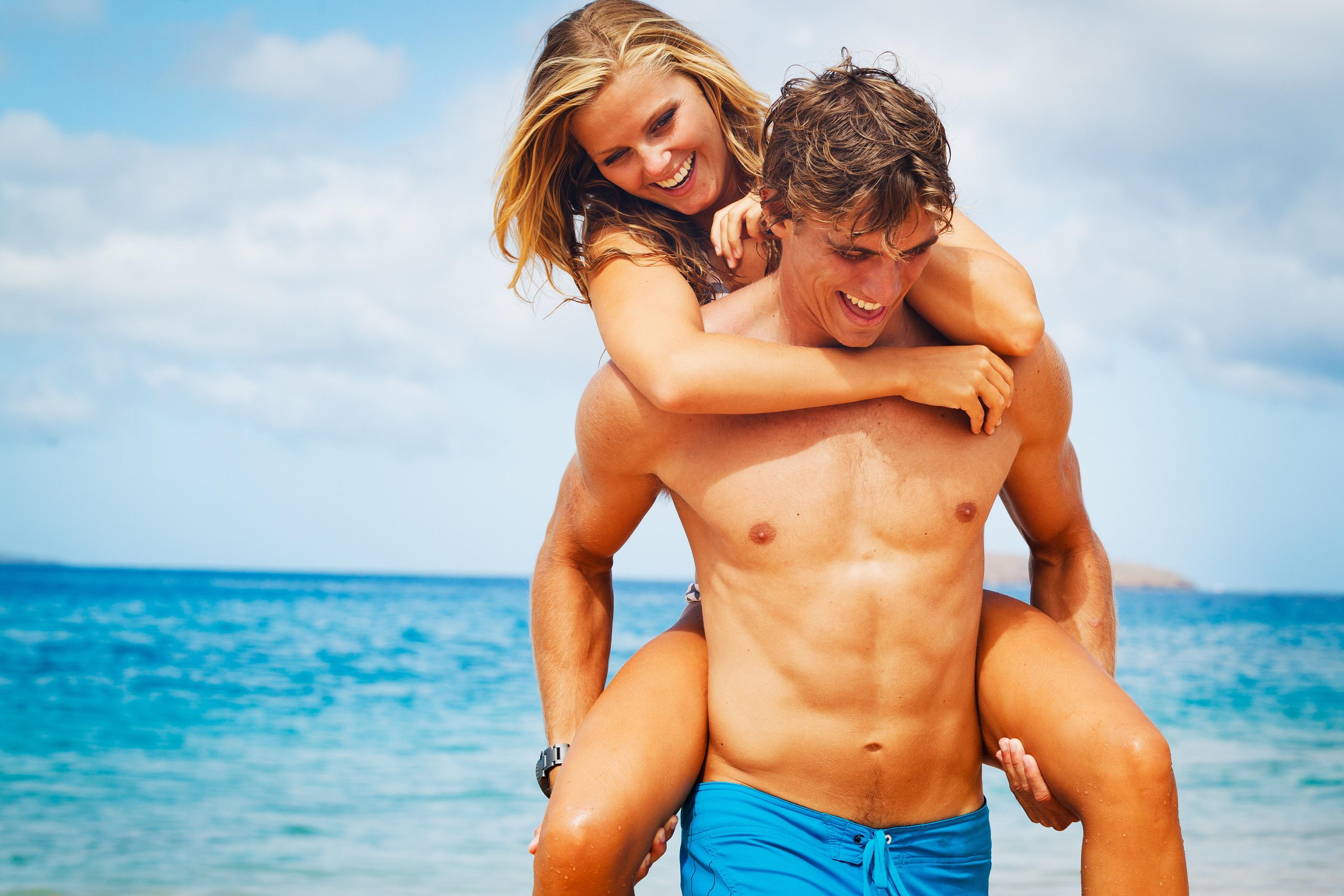 Mann trägt Frau auf dem Rücken am Strand