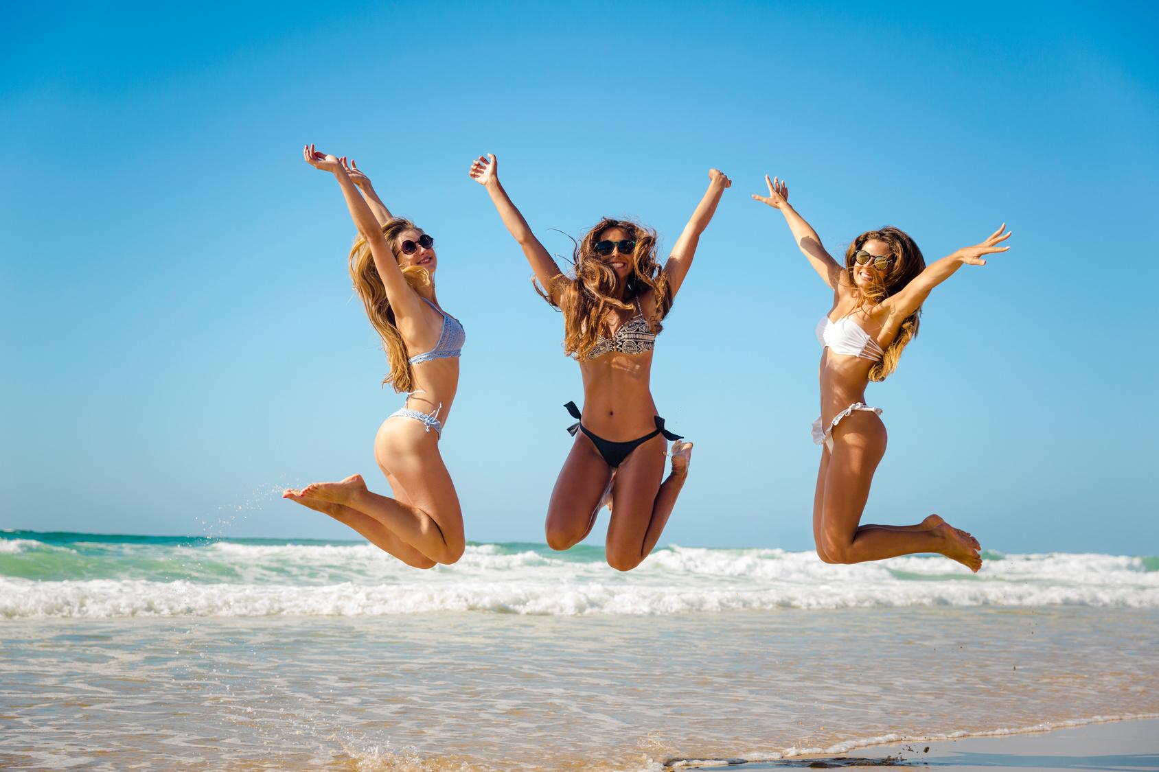 Three girls jumping on the beach