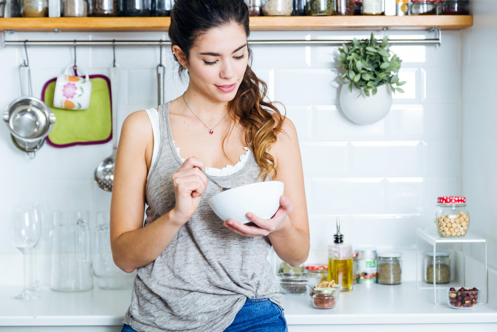 Frau frühstückt in der Küche