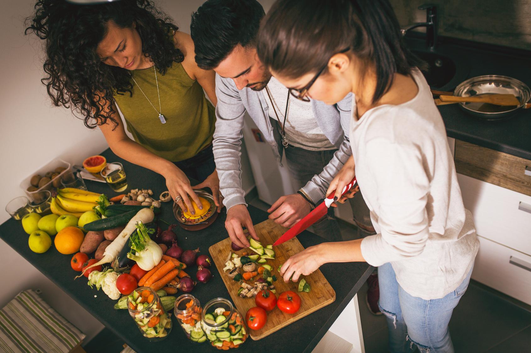 Drei Freunde bereiten gemeinsam in der Küche essen zu