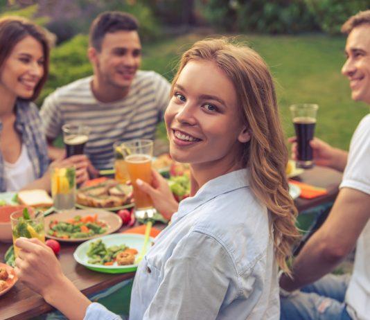 Vier Freunde sitzen beim gemeinsamen Essen im Garten