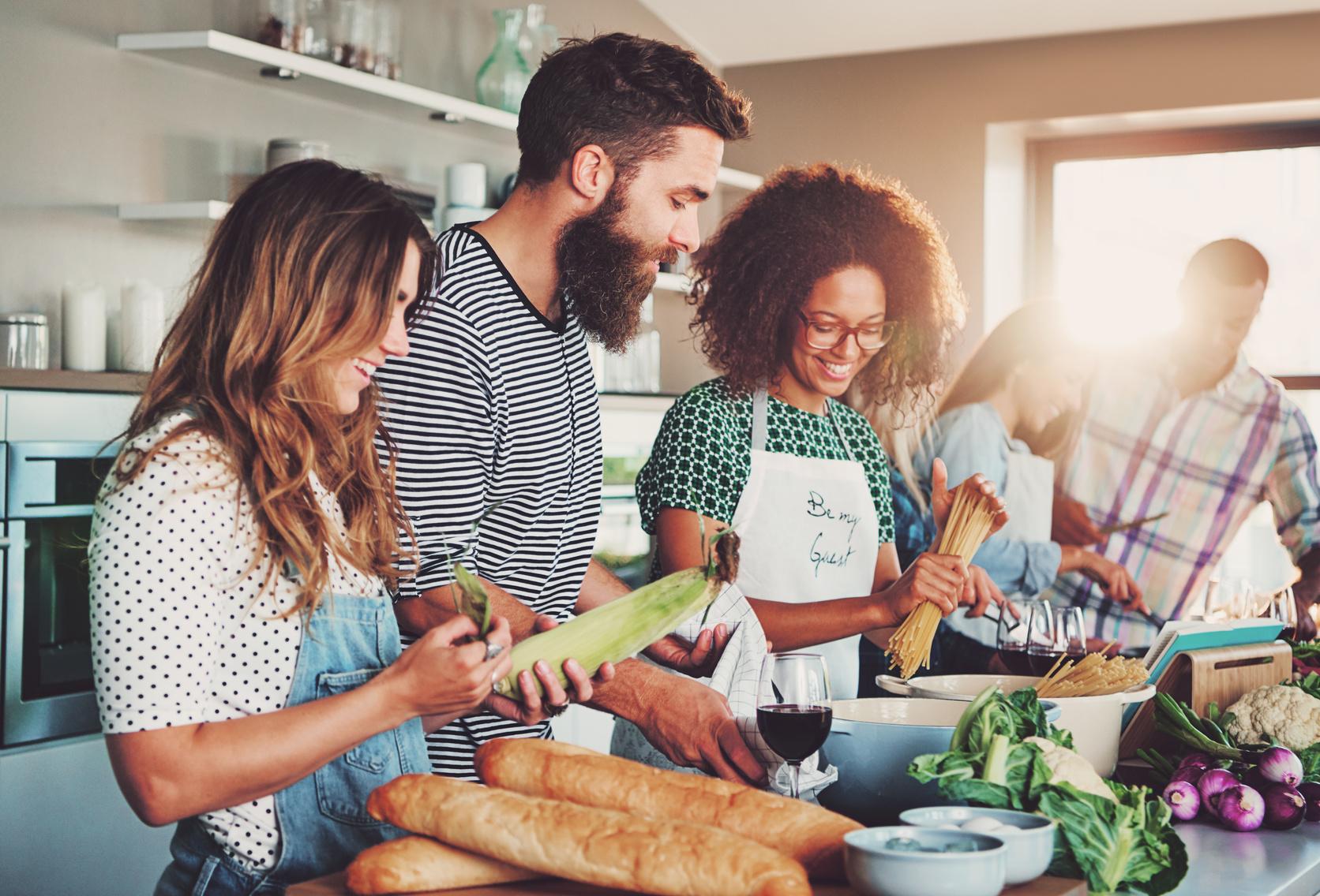 Freunde kochen gemeinsam und bereiten Essen in der Küche zu
