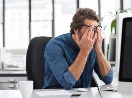 Mann sitzt gestresst am Arbeitsplatz vor seinem Computer und hält die Hände vor das Gesicht