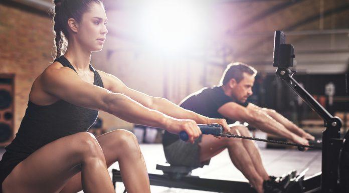 Mann und Frau trainieren im Fitnessstudio auf dem Rudergerät
