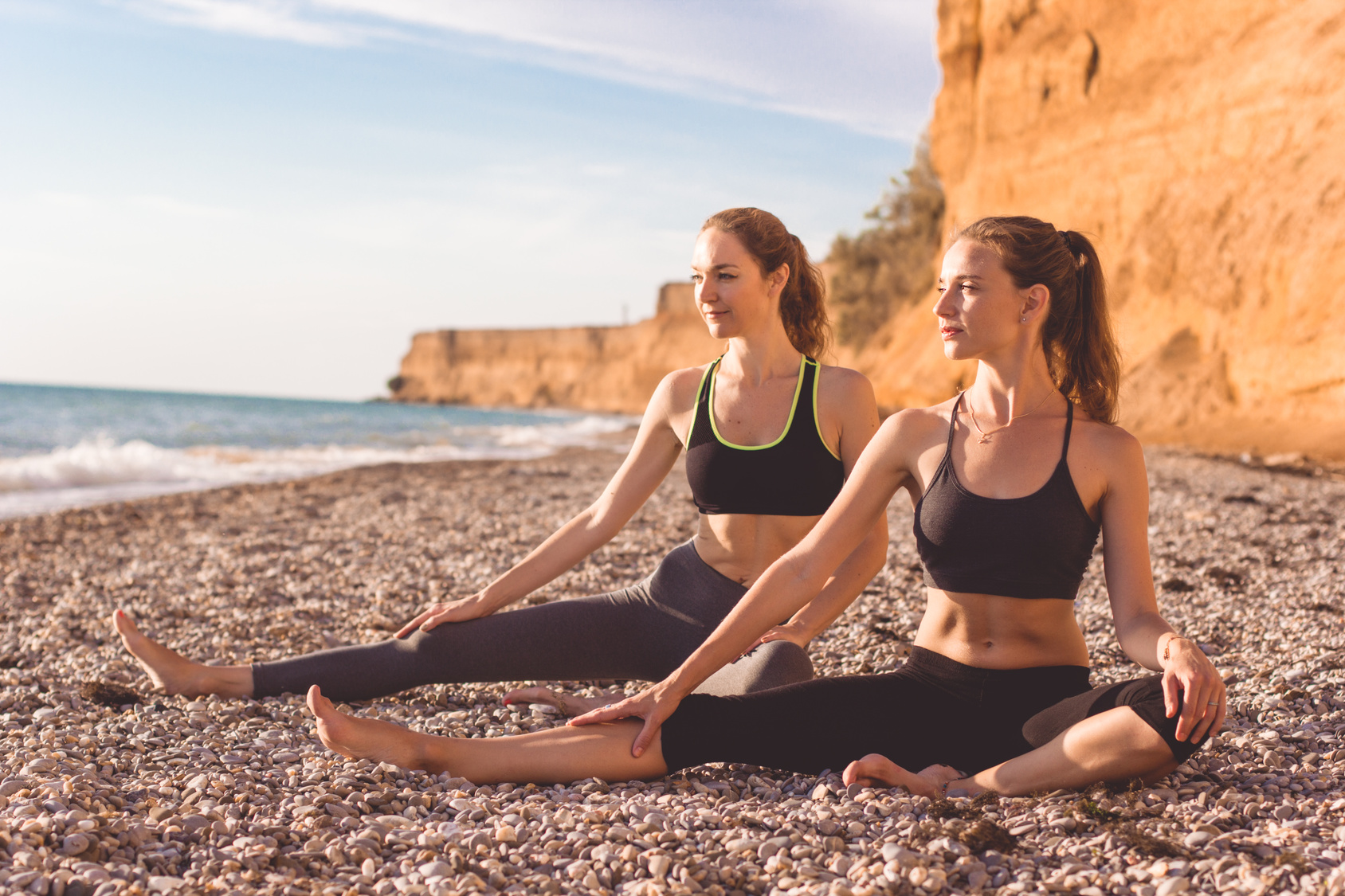 Zwei Frauen machen Yoga am Strand