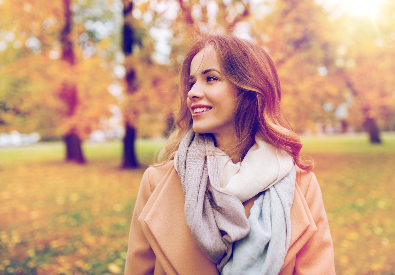 Frau lächelt während ihrem Spaziergang durch den Park im Herbst