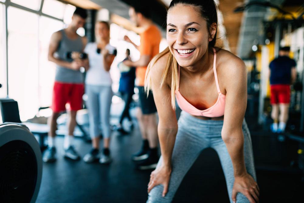 Frau im Fitnessstudio glücklich nach dem Training