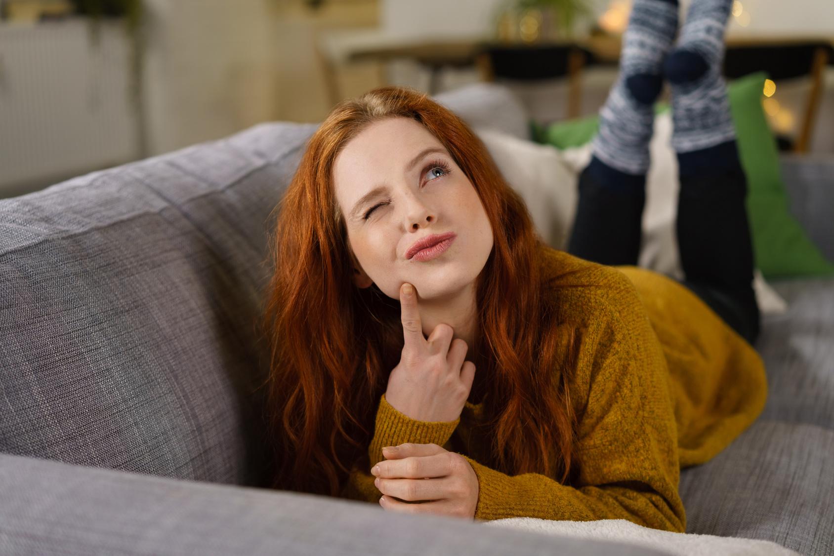 Frau liegt auf der Couch und denkt nach
