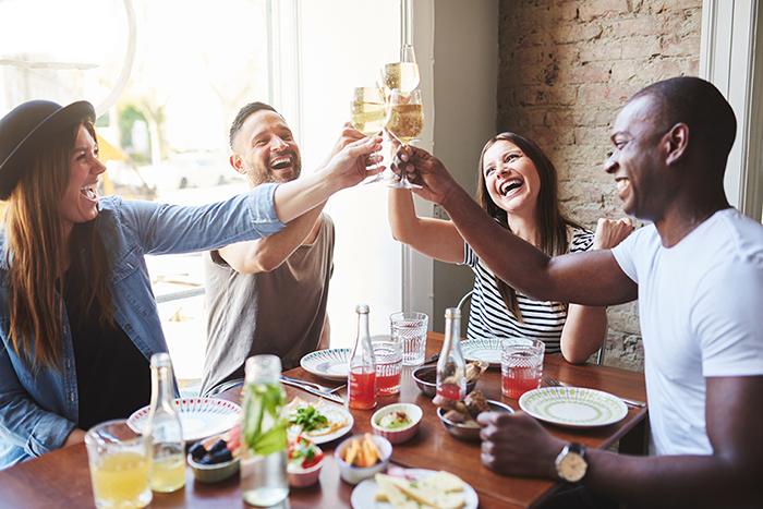 Vier Freunde essen gemeinsam zu Abend in einem Restaurant und stoßen mit Wein an