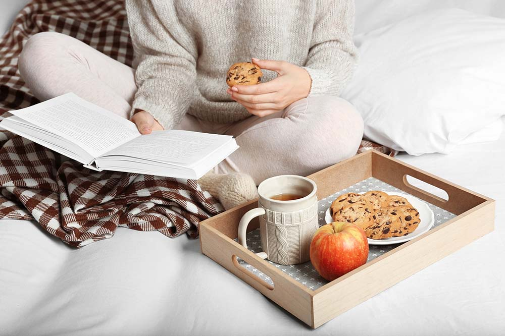 Frau sitzt auf der Couch liest ein Buch, trinkt Tee und isst Kekse