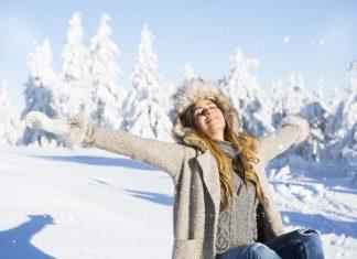 Abnehmen im Winter - Frau streckt Arme im Winter im schneebedeckten Wald