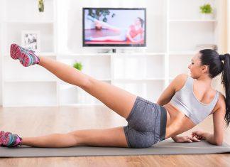 Frau macht Bauch-Beine-Po-Training zu Hause vor dem Fernseher