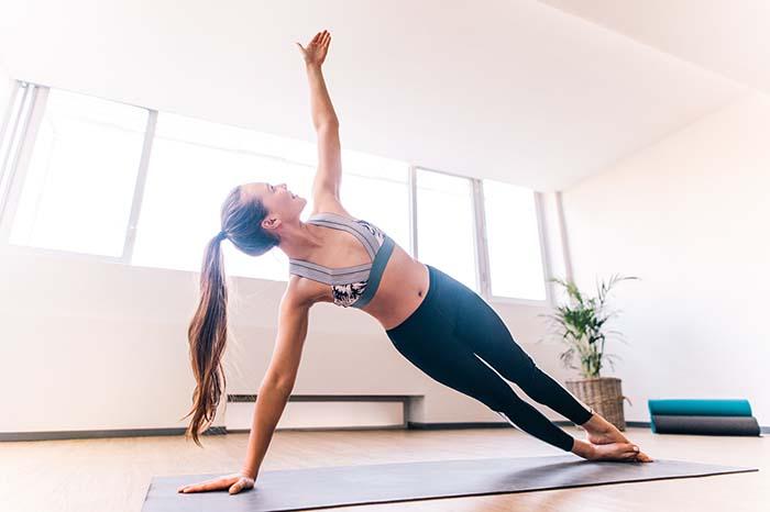 Frau macht Side Plank beim Training zu Hause