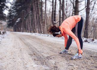 Frau dehnt sich vor dem Laufen im Winter