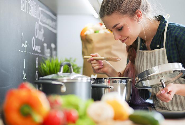 Frau kocht Suppe in der Küche