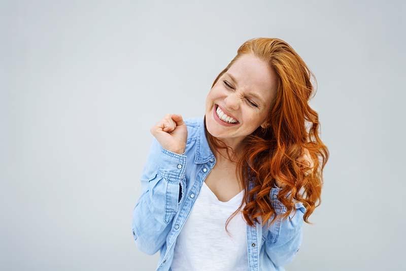 Rothaarige Frau freut sich und grinst
