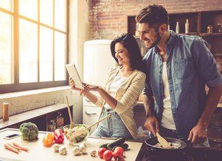 Paar stellt Ernährung um und kocht leckeres, gesundes Essen anhand eines Ernährungskonzeptes