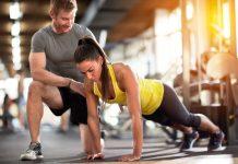 Frau lernt Liegestütze richtig zu machen mit einem Trainer