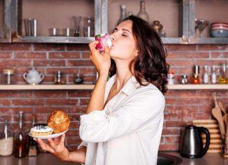 Frau in der Küche isst Kuchen aus Frust