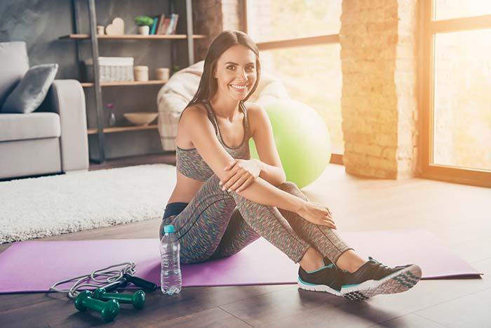 Frau sitzt auf der Trainingsmatte, bevor sie ihr Krafttraining zuhause startet