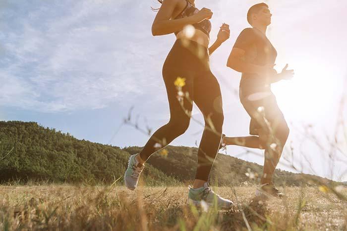 Paar joggt gemeinsam in der Natur bei Sonnenaufgang