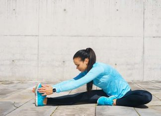 Frau sitzt am Boden und dehnt ihre Beine nach dem Training