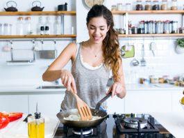 Frau kocht abends ohne Kohlehydrate und brät Zwiebeln in der Pfanne an