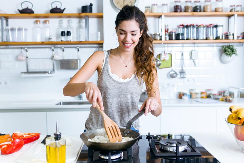 Junge Frau kocht abends ohne Kohlehydrate und brät Zwiebeln in der Pfanne an