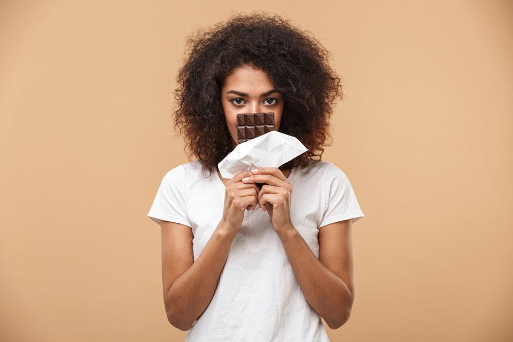 Frau mit einer Tafel Schokolade fragt sich, ob Abnehmen mit Schokolade möglich ist