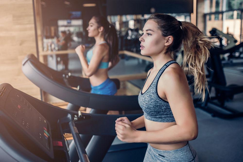 Zwei Frauen machen Cardio Training im Fitnessstudio auf dem Laufband