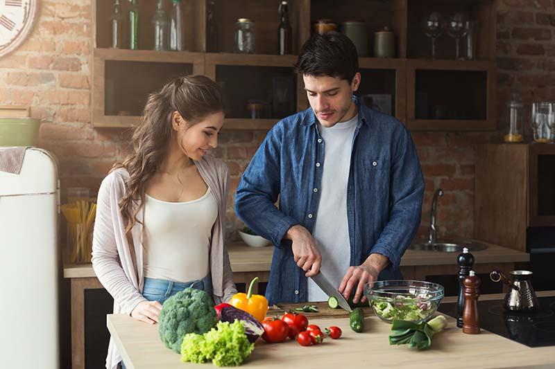 Paar kocht gemeinsam in der Küche ein gesundes Abendessen mit Gemüse